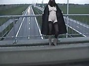 Exhibitionist wife in stockings and long coat flashing motorists on a bridge