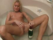 Horny blonde with pierced nipples masturbates in bathtub with bottle